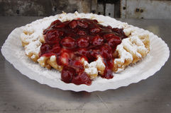 Funnel Cake. Fried dough funnel cake with sugar and cherry syrup toppings royalty free stock image