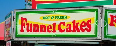 Funnel Cake stand at the Fair. Funnel cake is a regional food popular in North America at carnivals, fairs, sporting events, and seaside resorts. In some stock photos