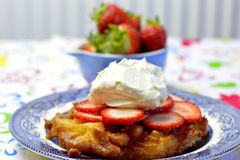 Funnel cake with strawberry and whipped cream. Funnel cakes are made by pouring batter into hot cooking oil in a circular pattern and deep frying the overlapping Royalty Free Stock Image