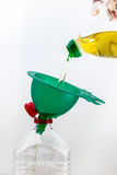 Funnel. Old frying oil pouring into another bottle with a green funnel royalty free stock image