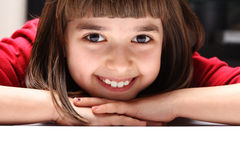 Funnily!. Girl 9 years old leaning on the table and laughs Royalty Free Stock Photo