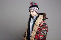Funnujongen in de winterbovenkleding het jonge geitje droeg al zijn kleren stock afbeelding