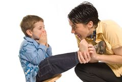 Funny. Mom tickling son's feet on white isolated background Royalty Free Stock Photo