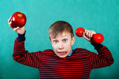 Funny active child holding red dumbbel and big apple Stock Images
