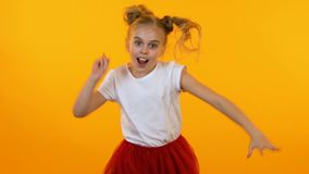 Funny active girl posing and dancing before camera, little model, slow motion. Stock footage stock video footage