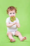 Funny adorable baby with a big candy Royalty Free Stock Photography