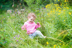 Funny adorable baby girl walking in the garden Stock Images