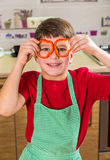 Funny adorable boy with sliced paprika on eyes. In the kitchen interior royalty free stock photo
