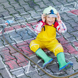 Funny adorable child of four years having fun with fire truck pi. Creative leisure for kids: cute kid boy in helmet having fun with fire truck picture drawing Stock Photos