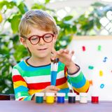 Funny adorable little kid boy with glasses holding watercolors and brushes. Happy child and student is back to school stock photos
