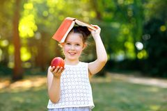 Funny adorable little kid girl with book, apple and backpack on first day to school or nursery. Child outdoors on warm royalty free stock photo