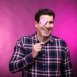 Funny adult man covering his right eye with a pink heart. Studio photo Stock Photos