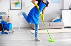 Funny adult woman moping floor. In living room Stock Photo