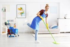 Funny adult woman moping floor in  room. Funny adult woman moping floor in living room Stock Photo