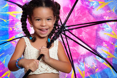 Funny african american small girl holding a huge colorful umbrel Royalty Free Stock Photos