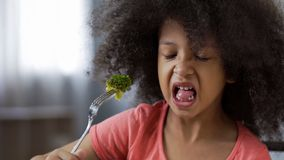 Funny African girl eating broccoli with huge disgust, healthy diet for children