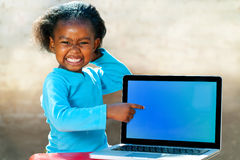 Funny african girl pointing at blank screen. Royalty Free Stock Photo