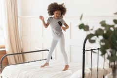 Funny african kid girl jumping on bed singing in hairbrush royalty free stock photography
