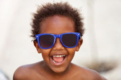 Funny Afro-American kid with blue sunglasses. And a beautiful smile Stock Photography
