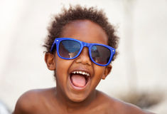 Funny Afro-American kid with blue sunglasses Royalty Free Stock Images