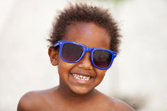 Funny Afro-American kid with blue sunglasses Royalty Free Stock Photos