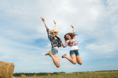 Funny air jump of two college friends on summer rural vacations Stock Image