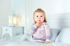 Funny amazed blond little girl sitting on bed in bedroom. White interior, big bed, bedside table and night lamp. Girl touches her mouth by hand Stock Photos
