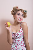 Funny amazed pin up girl in curlers with apple Royalty Free Stock Image