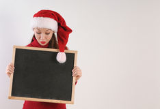 Funny amazed young woman with blackboard in santa hat on white b Royalty Free Stock Images