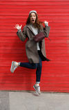 Funny amazed young woman jumping in the air. Over red wall background Stock Photo