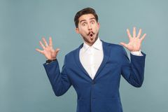 Funny amazing manager open mouth, big eyes and shouting. Business people concept, richly and success. Indoor, studio shot on light blue background Stock Photo