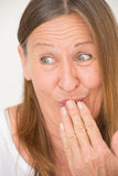 Funny amused happy mature woman. Portrait amused attractive mature woman with funny laughing facial expression, covering mouth with hand, bright background Stock Photos