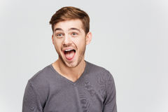 Funny amusing young man in grey pullover screaming. Over white background Stock Photography