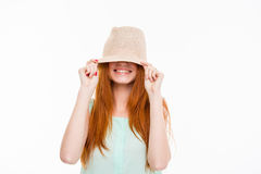 Funny amusing young woman hiding under boonie hat. Funny happy smiling amusing young woman with long red hair hiding eyes under boonie hat posing on white stock photos