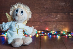 Funny angel and bright lights garlands on wooden boards Royalty Free Stock Photography