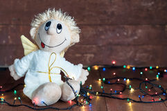 Funny angel and bright lights garlands on wooden boards Stock Images