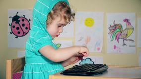 Funny angry cute girl using playing with keyboard from computer