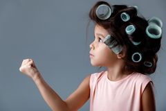 Cute little child girl in pink dress and hair curlers. Funny angry cute little child girl in pink dress and hair curlers posing on gray background. Human stock photos