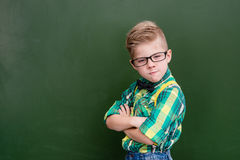 Funny angry nerd near empty green chalkboard Royalty Free Stock Photos