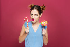 Funny angry young woman holding candy cane and colorful lollipop Royalty Free Stock Photo