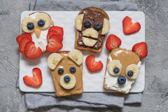 Funny animal faces toasts with banana, strawberry and blueberry. Funny animal faces toasts with spreads, banana, strawberry and blueberry stock photos