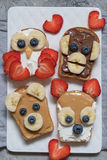Funny animal faces toasts with banana, strawberry and blueberry. Funny animal faces toasts with spreads, banana, strawberry and blueberry stock photography