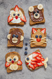 Funny animal faces toasts. With spreads, banana, strawberry and blueberry royalty free stock photos