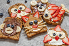 Funny animal faces toasts. With spreads, banana, strawberry and blueberry royalty free stock images