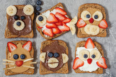 Funny animal faces toasts. With spreads, banana, strawberry and blueberry royalty free stock image