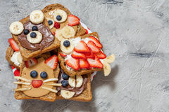 Funny animal faces toasts. With spreads, banana, strawberry and blueberry stock photo