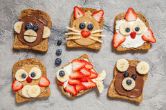 Funny animal faces toasts. With spreads, banana, strawberry and blueberry royalty free stock photography