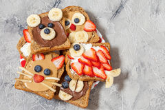 Funny animal faces toasts. With spreads, banana, strawberry and blueberry stock photography