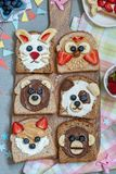 Animal faces toasts with spreads, banana, strawberry and blueberry. Funny animal faces toasts with spreads, banana, strawberry and blueberry royalty free stock image