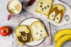 Funny animal sandwich for kids shaped cute bear, panda, fox, rabbit. With peanut butter, honey, chocolate paste and banana. Top vew stock photos